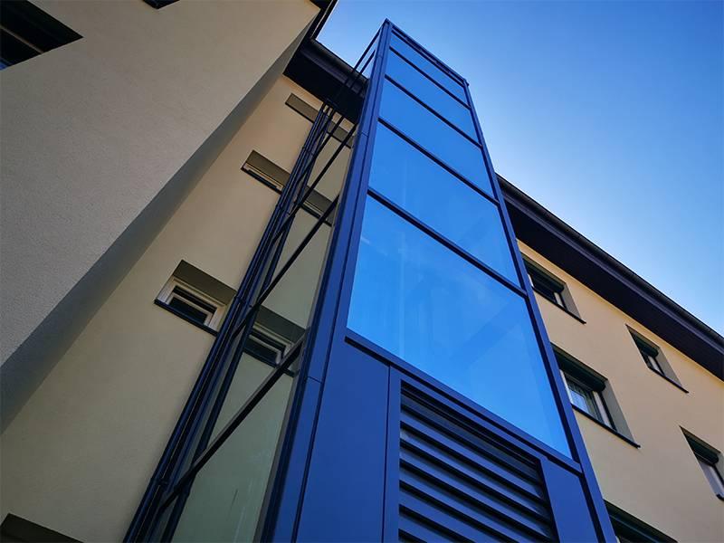 Stahl-Glas Einhausung bei nachträglich errichtetem Wohngebäude Aussenlift