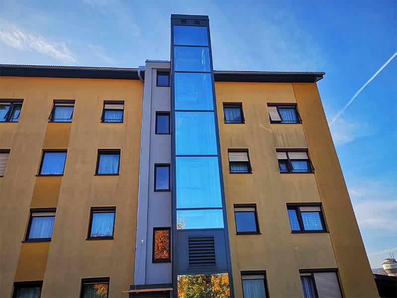 Stahl-Glas Einhausung bei nachträglich errichtetem Wohnhaus Aussenlift