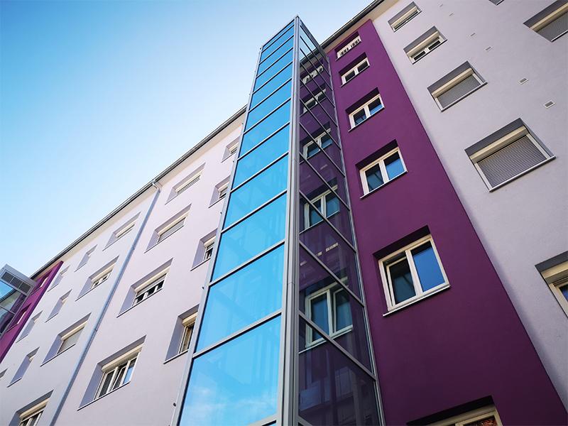 Stahl-Glas Einhausung bei nachträglich errichtetem Wohnhaus Aufzug aussenliegend